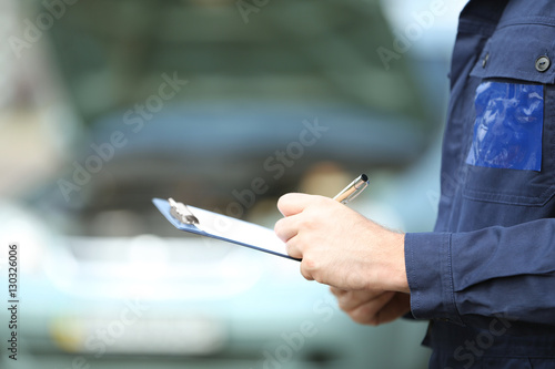Fotografía  Mechanic standing in front of an open car hood with clipboard and pen