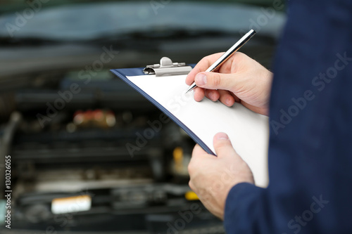 Pinturas sobre lienzo  Mechanic standing in front of an open car hood with clipboard and pen