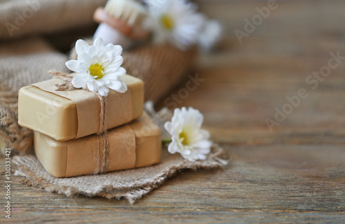 Poster Spa Spa concept. Soap and daisy flowers on wooden table