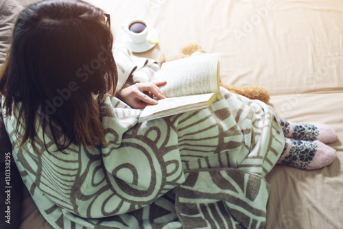Woman wrapped in a warm blanket reading book Poster