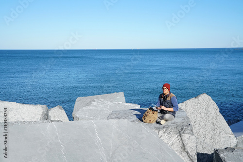 Valokuva  Young reporter connected on tablet by the ocean