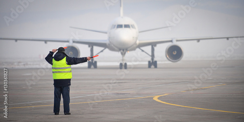 Photo  airport worker signaling