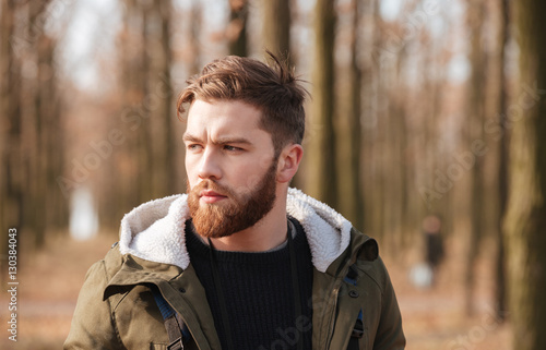 Fotografía  Handsome bearded man standing in the forest.
