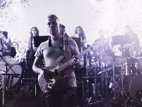 Staande foto Muziekband Guitarist performing on stage. Concert.