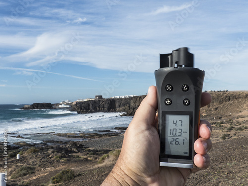 Hand holding up a wind anemometer, wind meter in the air, measur