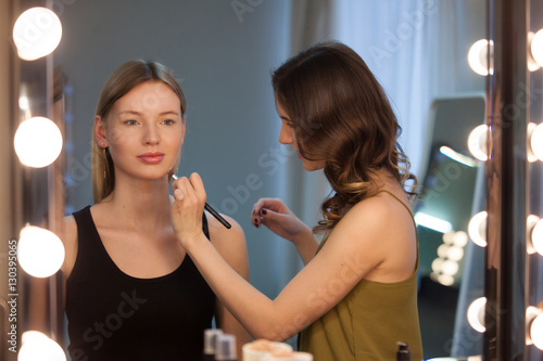 Valokuva  Makeup artist applies makeup to attractive blonde girl at the mirror with lamps in the beauty studio