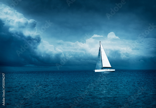 Stickers pour porte Voile White Yacht Sailing in Stormy Sea. Dark Thundery Night Background. Dramatic Storm Cloudscape. Danger in Sea Concept. Cold Toned Photo with Copy Space.