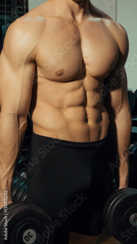 Fototapety, obrazy: Muscular guy in the gym with dumbbells