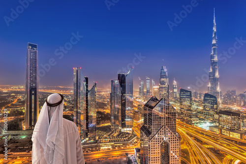 Poster Dubai Arabian man watching night cityscape of Dubai with modern futuristic architecture in United Arab Emirates