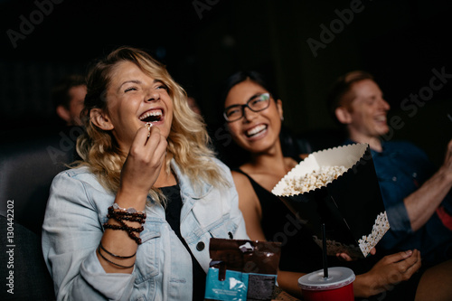 Young woman with friends watching movie