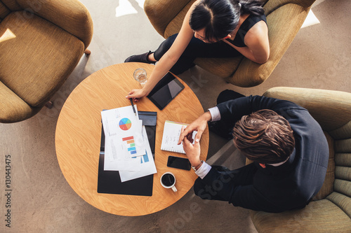 Business colleague sitting at table with charts Canvas Print