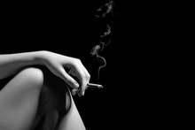 Female Hand With Smoking Cigarette On Naked Knee At Black Background With Copyspace, Monochrome