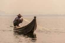 A Fisherman Pulls In His Net On Indawgyi Lake In Kachin State