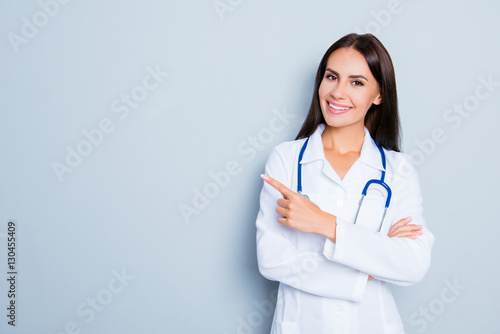 Fotografia  Smiling happy doctor pointing with finger on blue background