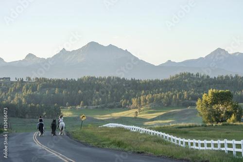 Photo Girls bareback riding horses on rural mountain road