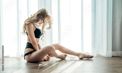 Poster Artist KB Alluring blond woman sitting on the wooden floor