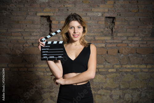 Fotografía  Young blonde actress smiling with movie clapper