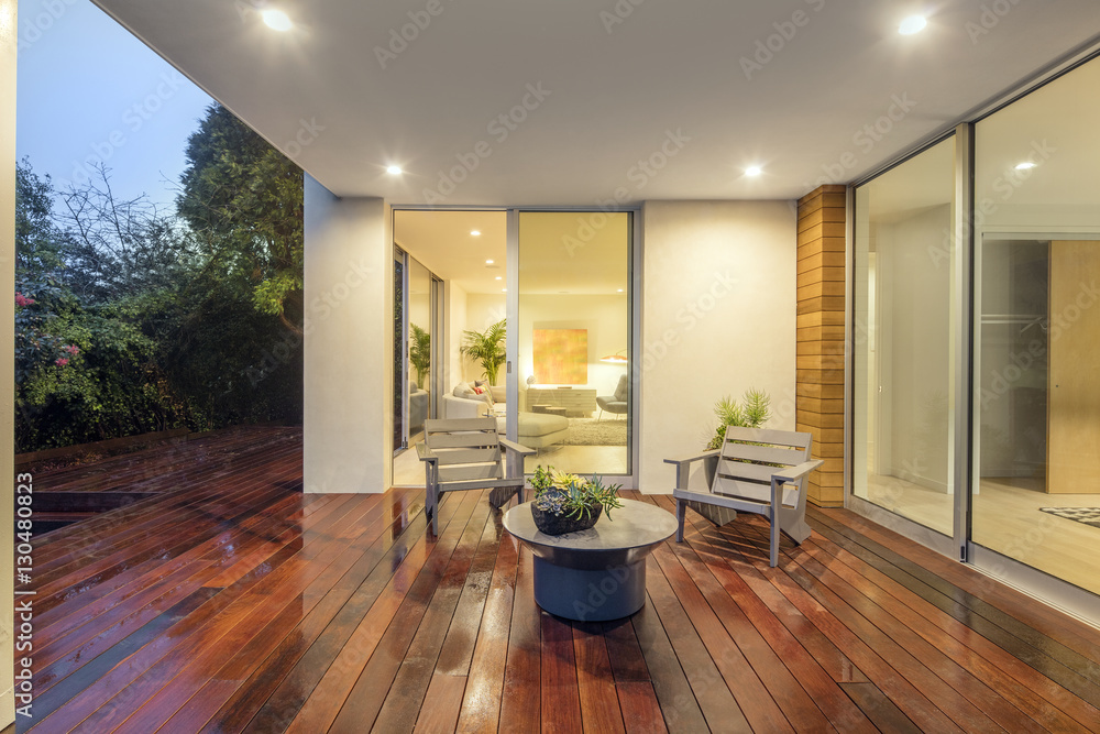 Wooden deck / balcony at night with furniture and open doors lea ...
