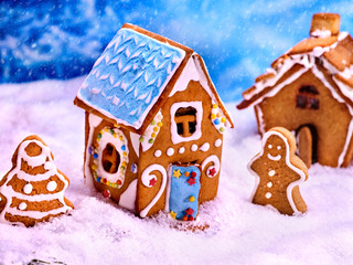 Street of gingerbread houses for Christmas. Gingerbread man and gingerbread Christmas tree in snow. Snowfall. Child craft.