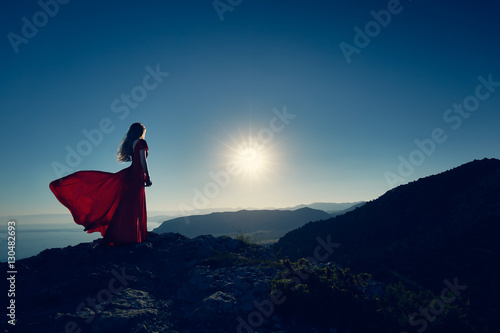 Foto op Aluminium Nachtblauw Young beautiful woman in red dress looking to mountains sea. Girl on the nature on blue sky background. Fashion photo