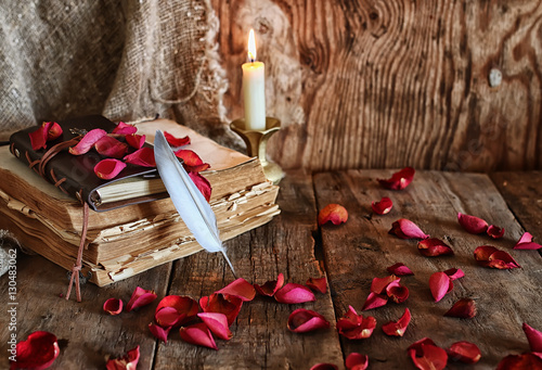 Fotografia  feather and book novel close to the a candle
