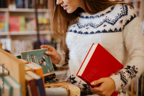 Photographie Young woman choosing books in library