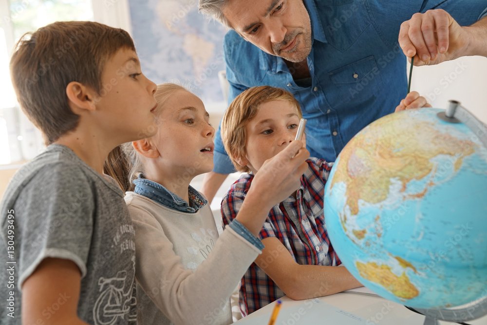Fototapety, obrazy: Teacher with kids in geography class looking at globe
