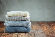 Stack Of Knitted Winter Clothes On Wooden Background, Sweaters, Space For Text. Toning Image