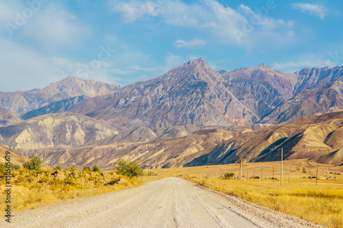 Foto op Aluminium Blauw The road and magnificent view of colourful mountain landscape in the centre of Kyrgyzstan, Naryn province right on the border with Jalal-abad province. Central Asia