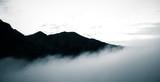 Piękny monochromatyczny widok na góry z rosnącymi chmurami - 130515875