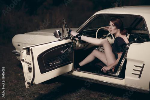 Photo  Junge attraktive Frau trägt 50/60er Jahre retro Fashion in einem Ford Mustang Ol