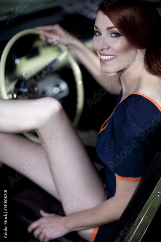 Foto  Junge attraktive Frau trägt 50/60er Jahre retro Fashion in einem Ford Mustang Ol