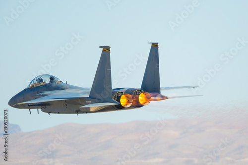 fototapeta na szkło F-15 Eagle against the Nevada hills, with afterburner on