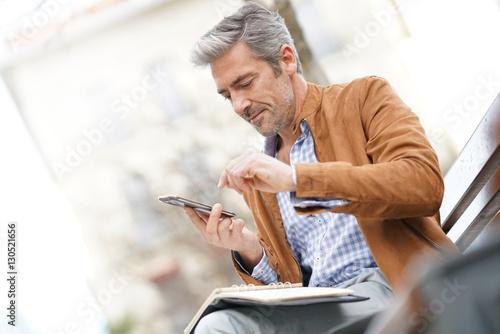 Foto  Businessman sitting on public bench, scheduling working day