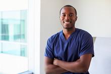 Portrait Of Male Nurse Wearing Scrubs In Exam Room