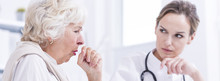 Senior Woman Coughing At The Doctor