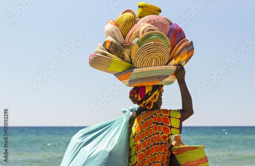 donna africana immigrata che vende cestini in Italia lungo la spiaggia Canvas Print