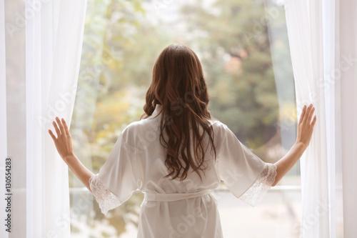 Fotografija Beautiful woman in white silk robe standing near window