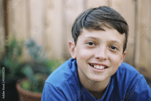 Portrait of smiling boy in backyard against wooden fence