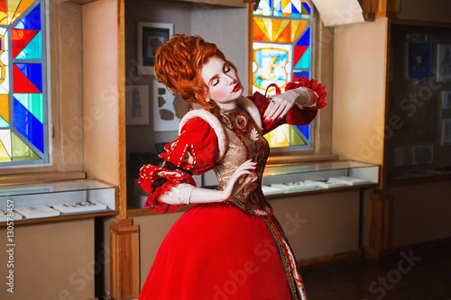 Cadres-photo bureau Carnaval Red-haired girl with blue eyes in red dress. Queen with a high hairdo. Vintage image. A woman with pale skin