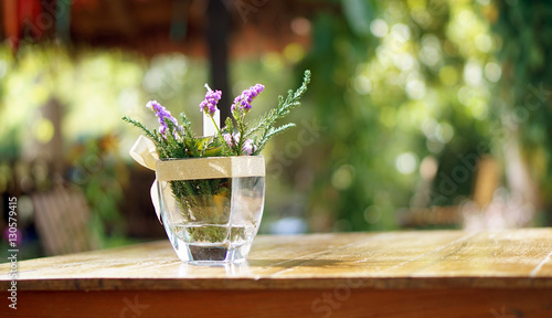 Valokuva  purple flower in vase on wood table copy space blur nature backg