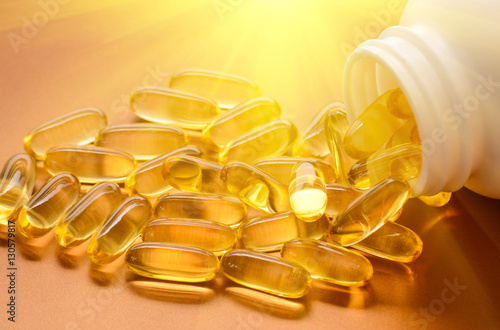 Fotografia  Fish oil capsules with omega 3 and vitamin D in a plastic bottle on a shiny text