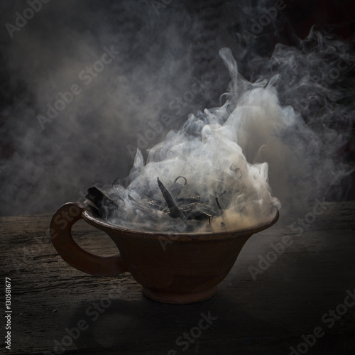 Wall Murals Nepal Steaming clay cup with spices on wooden table in street. Still life black background, Nepal.