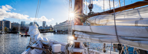 Voile Seattle sailing on Lake Union in a vintage yacht sailboat. Sun flare on mast