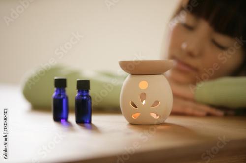 Fotografie, Obraz  Woman lying beside an aromatherapy burner