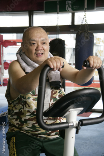 Fotografie, Obraz  A man on an exercise bike