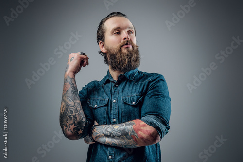 Photo  Bearded man with tattoos on arms.