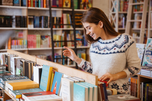Photographie  Beautiful brunette woman looking for a book in store