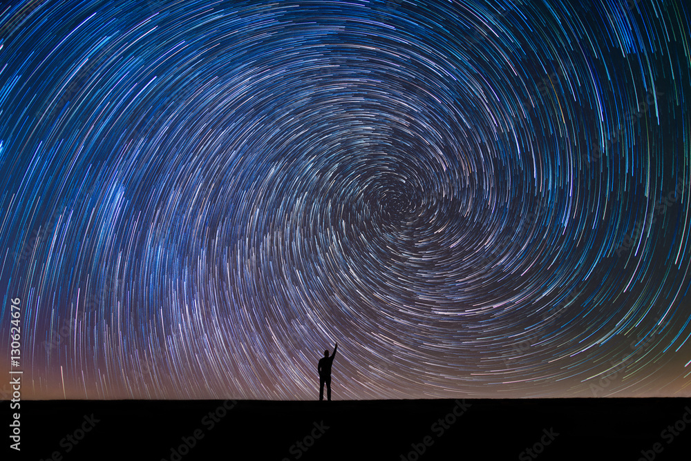 Fototapeta Silhouette of a man pointing at the north star vortex star trail