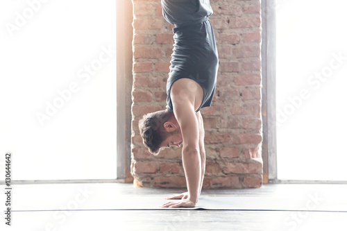 Fotografia  Sport. Strong young athlete doing exercise. Handstand
